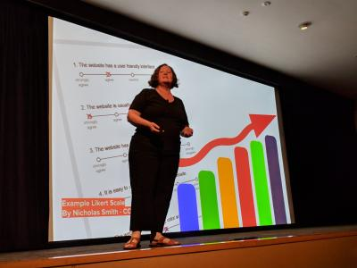 Donna speaking in front of a large screen showing a survey and colourful graph. Photo Credit: Josh Simmons