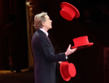 A man juggling 3 red hats. Photo by Usien on wikimedia commons.